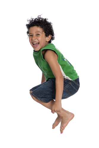 boy with curly hair in green top jumping up in air