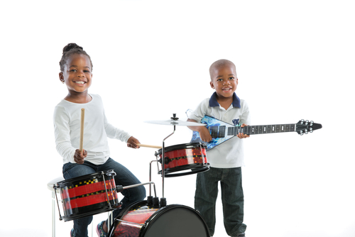One child playing drums another playing a guitar