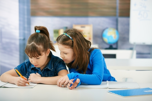 Two young girls studying together