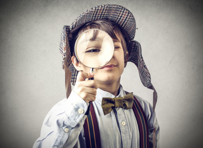 child wearing detective hat looking through magnifying glass