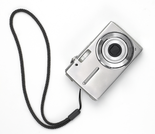 A silver digital camera with strap