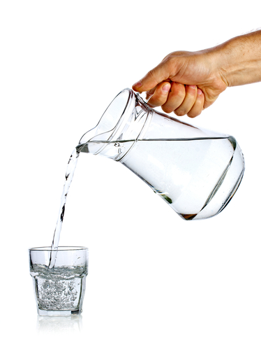Hand pouring a jug of water into a glass