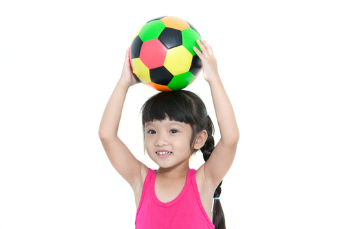 Little girl holding a ball on her head
