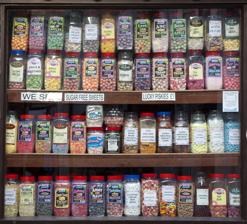 POLPERRO, ENGLAND - AUGUST 26: Jars of sweets displayed in a traditional sweet shop window, August 26, 2013 in Polperro, Cornwall, England. - stock photo