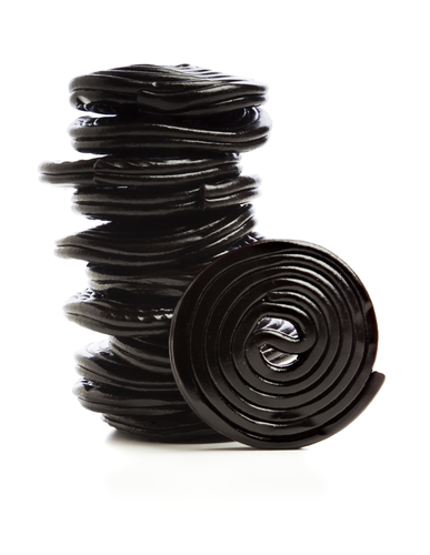 Stack of liquorice reels isolated on white - stock photo