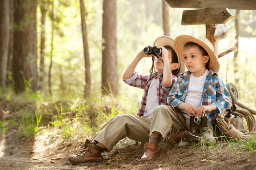 Two boys looking out binoculars