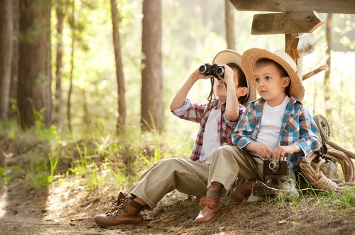 Two boys looking out binoculars