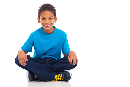 young boy sitting with legs crossed