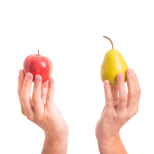 Two hands holding an apple and a pear