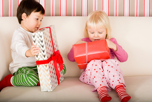 Two children on sofa opening Christmas presents