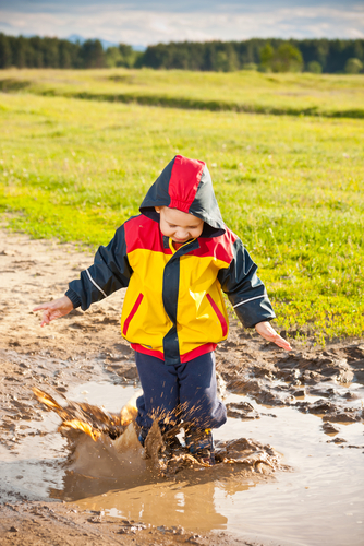 Boy in muddy puddle