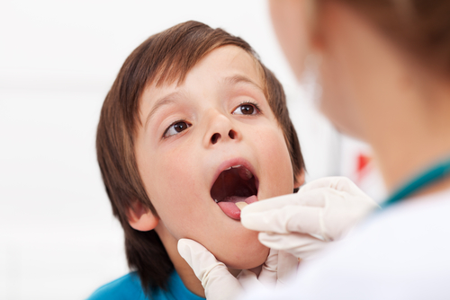 doctor looking in a boys mouth