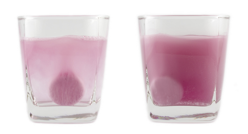 Pink fizzing tablet in water