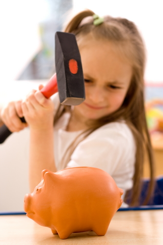 Girl about to smash a piggy bank with a hammer