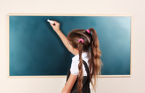 a girl writing with chalk on a blackboard