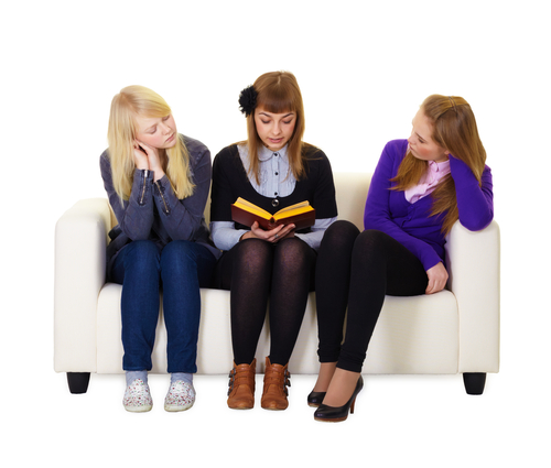 Girls sitting on a sofa reading