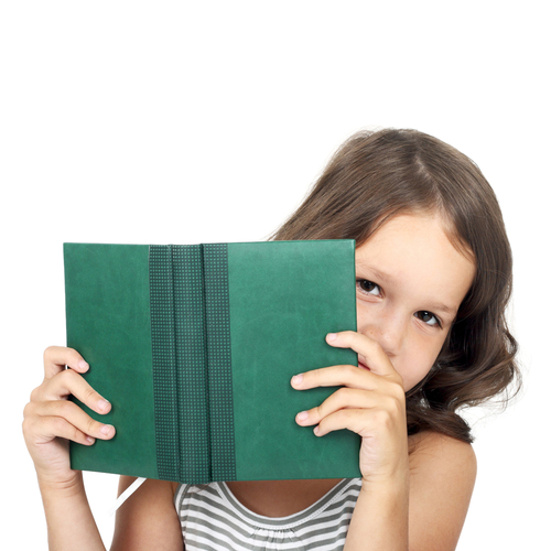 Little girl peeking from behind a book