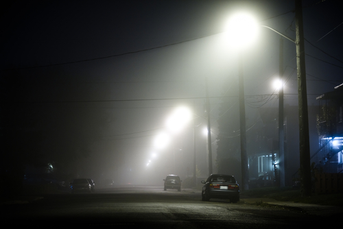 Foggy road at night with cars parked at the side