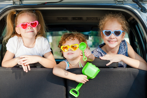 Three children looking out the boot of a car